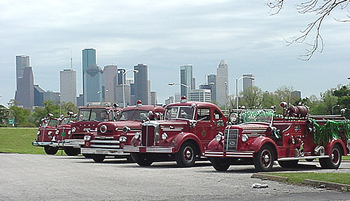 Antique firetrucks with the houston skyline as the background.